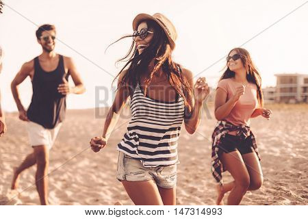 Carefree run. Group of young cheerful people running along the beach and looking happy