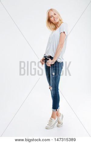 Full length portrait of a smiling young woman standing with hands in pockets on tiptoe isolated on a white background