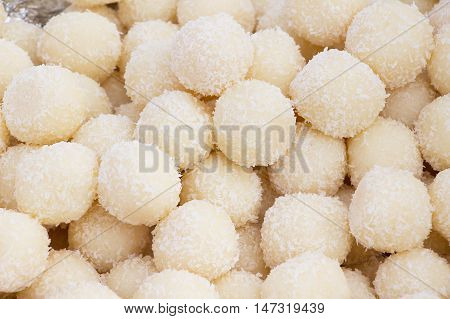 Sweet coconut balls as a background. Sweet balls of condensed milk and coconut. Vedic cooking.