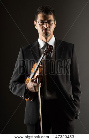 Violinist  playing violin on dark background,
