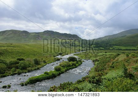 Dingle river with cloudy sky and hills