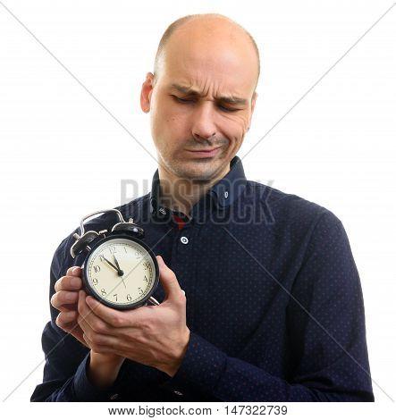 Sceptical Bald Man Holding An Alarm Clock