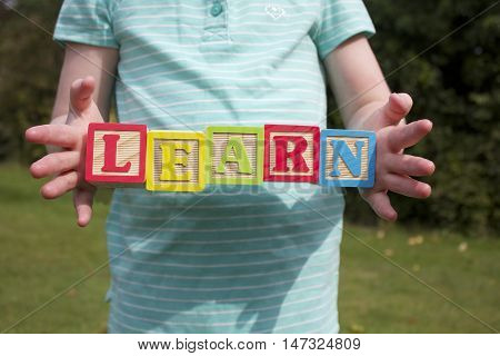 A girl holding wooden blocks spelling the word 'LEARN'. The girl is outdoors on a green background.