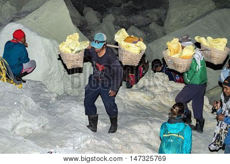 Java, Indonesia - August, 9, 2016 - Miners Carrying Sulfur From Ijen Volcano Blue Flames At Night