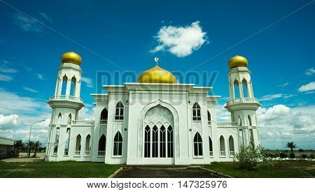 the big white place of worship of Muslim with gold roof on top