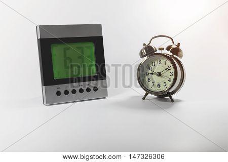 Digital and analog alarm clock on white background.