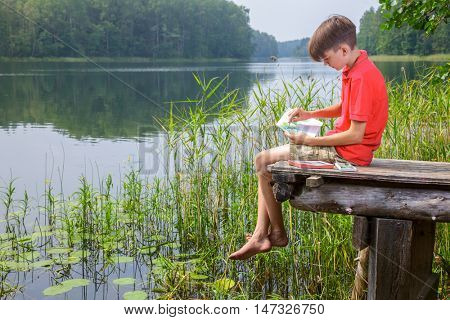Scenery painter boy sitting on a wooden dock at a summer forest lake drawing with pastel sticks