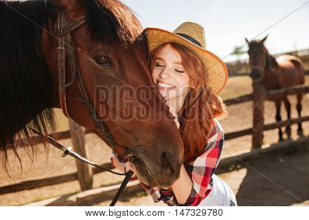 Happy tender young woman cowgirl standing and hugging her horse
