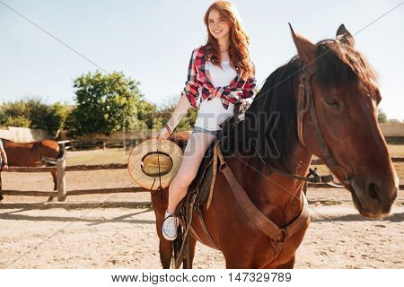 Smiling attrative young woman cowgirl riding horse in village