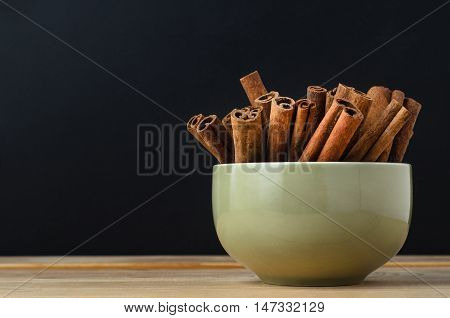 Green Bowl Of Cinnamon Sticks On Wood With Black Background