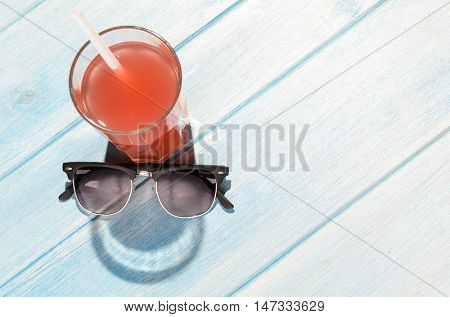 creative summer smile. red drink in glass on blue summer table