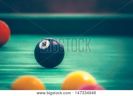 Black billard ball number eight on green billard table