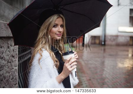 Cheerful woman under umbrella in the street drinking morning coffee. Walking girl