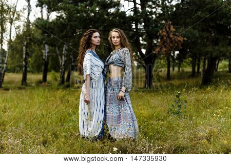 Young girls in ethnic clothes walking in fields. Fashion photo, folklore style
