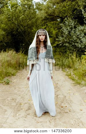 Young girl in traditional folk Crimean Tatar clothes walking in fields