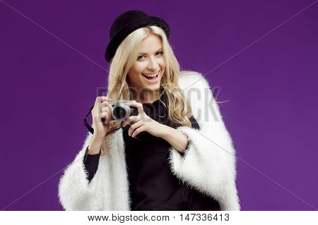 Fashion young girl makes photo. Purple background. Photographer