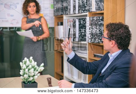 Businessman raising pencil in his hand while having question to female coach after business meeting in headquarters