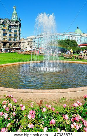 ST PETERSBURG RUSSIA-AUGUST 4 2015. Kazan Square in summer day- small fountain and pink peonies on the foreground and historic buildings of Nevsky Prospect on the background in St Petersburg Russia
