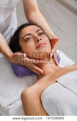 Head massage in spa. Female beautician doctor with patient in wellness center. Professional cosmetologist make face procedure to beautiful indian girl in cosmetology cabinet or beauty parlor.