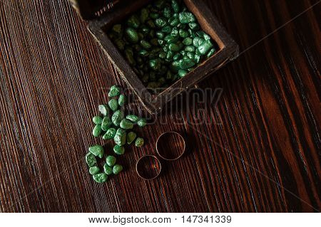 wedding rings with green stoun on table