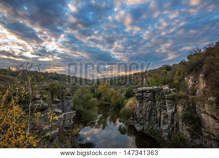 Buky Canyon (River Hirs'kyi Tikych - Ukraine) in autumn season. Sky with clouds is multicolored.
