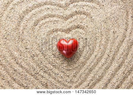 Red Heart Shaped Stone On Sand Surface Forming Heart Waves