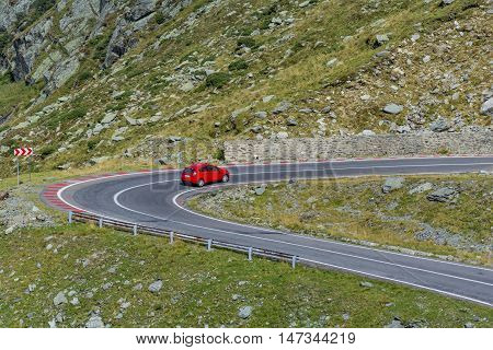 Red car on Transfagarasn winding mountain road with at high altitude in Carpathian Mountains