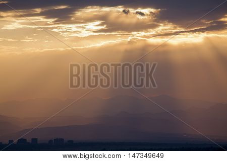 Dramatic Evening Cloudscape over Mountain Range with City Buildings