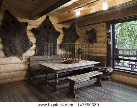 The interior of the hunter's house with the skins of wild boars hung on the walls