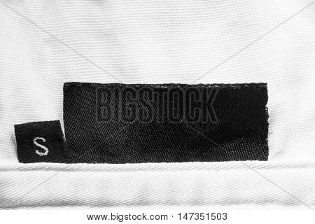 Black blank clothes label on white cloth as a background