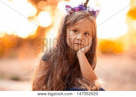 Cute kid girl 4-5 year old wearing unicorn headband outdoors at sunset.