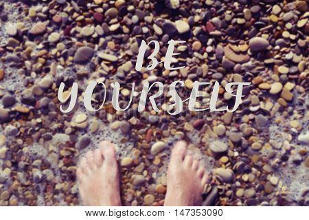 high-angle shot of the bare feet of a young caucasian man in the seashore of a shingle beach, and the text be yourself