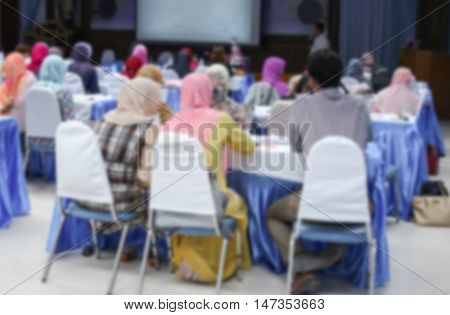 blurred abstract background of university students. sitting in a lecture room with a teacher in front of the class with white projector slide screen