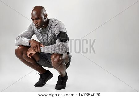 African Male Model Crouching On Grey Background