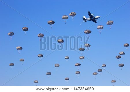 paratrooper jumping from their planes in a blue sky