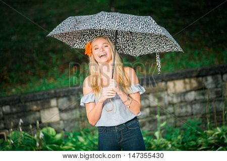 High School Senior Poses With Umbrella For Portraits On A Rainy Day