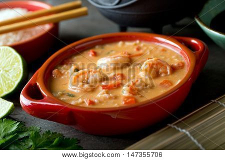 A bowl of delicious Thai red curry coconut shrimp soup with rice.