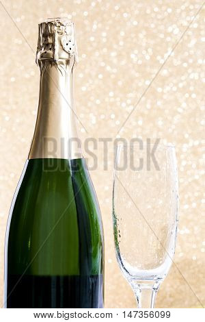 Bottle of champagne and glass cup on golden background