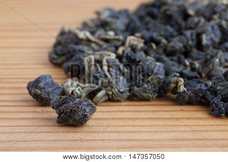 leaves of green tea on the wooden table