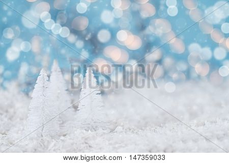 Miniature white Christmas trees against snowy bokeh background with lights. Macro with extreme shallow depth of field and selective focus on tree in foreground. Room for copy space.