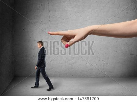 Businessman following direction that big female's hand pointing out. Rebuke and telling off. Upbraid and reproach. Boss and empolyee.