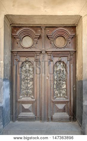 Weathered wooden door with forged grill background