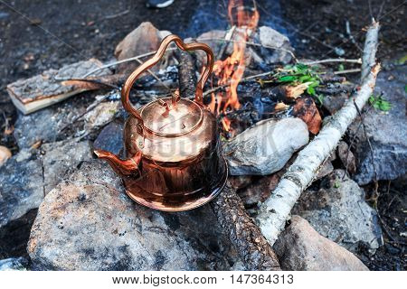Metal camp kettle hanging over the coals campfire poster