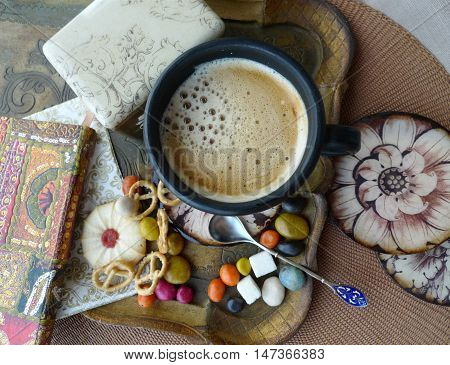 Retro still life. A cup of coffee with cream, biscuits and sweets on a tray. Decoupage.