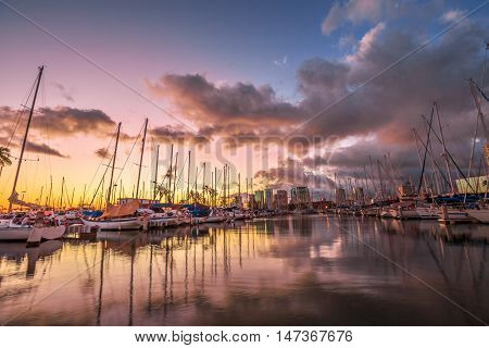 Dramatic landscape of sailing boats and yachts docked at the Ala Wai Harbor the largest yacht harbor of Hawaii reflecting in the sea at sunset. Honolulu Oahu Hawaii.
