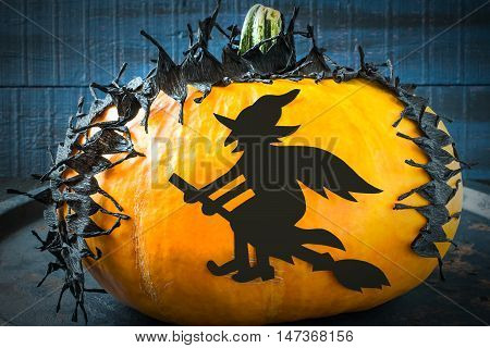Idea homemade decorating for Halloween. Application: barbed tape made of black crepe paper and a witch on pumpkin. The original design in the style of Halloween. Tinted photo