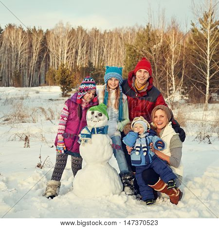 portrait of a cheerful family with snowman. happy children and parents in the winter outdoors