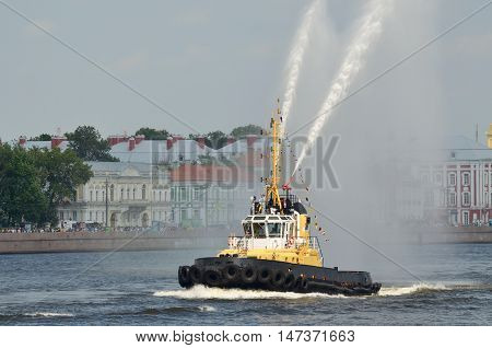 Marine boat tug boat on the river shows beautiful fountains from the water.