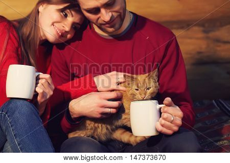 man and woman  drinking tea at his home. young couple in love with mugs in hands and cat