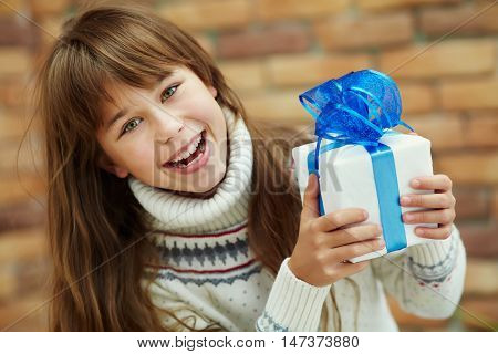 Cute happy teenage girl holding a gift. xmas kid